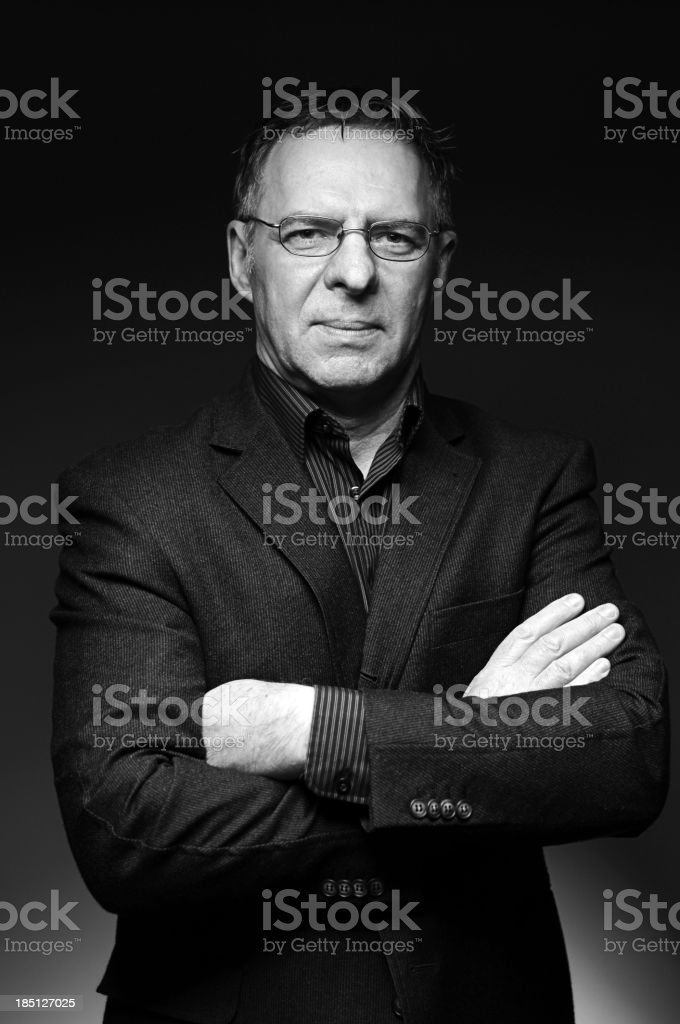 A portrait of a mature businessman in a black suit royalty-free stock photo
