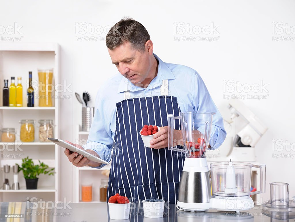 Portrait Of A Mature Caucasian Man Using An Online Recipe royalty-free stock photo