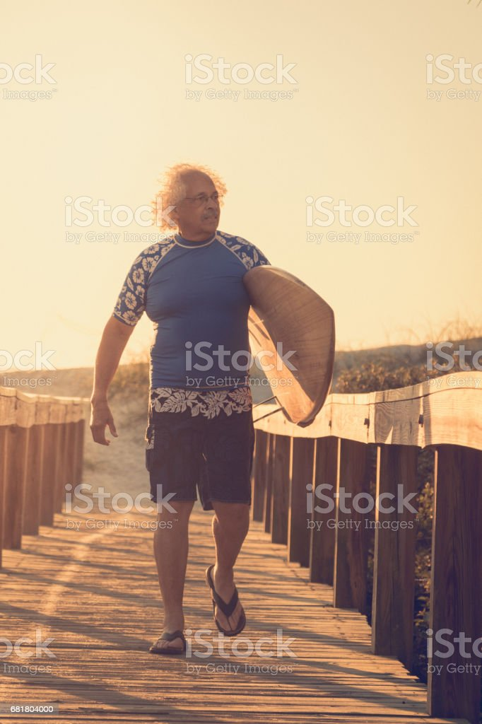 Portrait of a mature surfer at sunrise stock photo