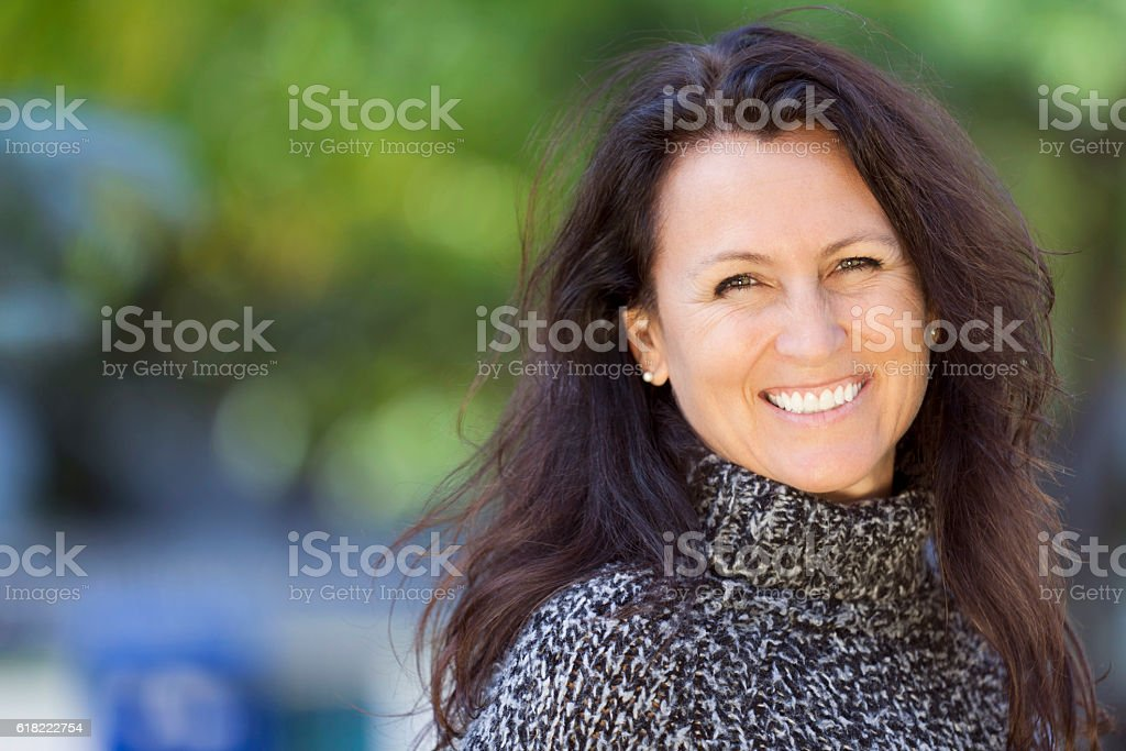 Portrait Of A Mature Woman Smiling At the Camera At The Park stock photo