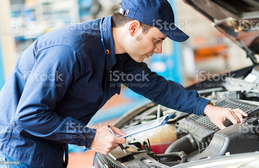 Portrait of a mechanic at work in his garage stock photo