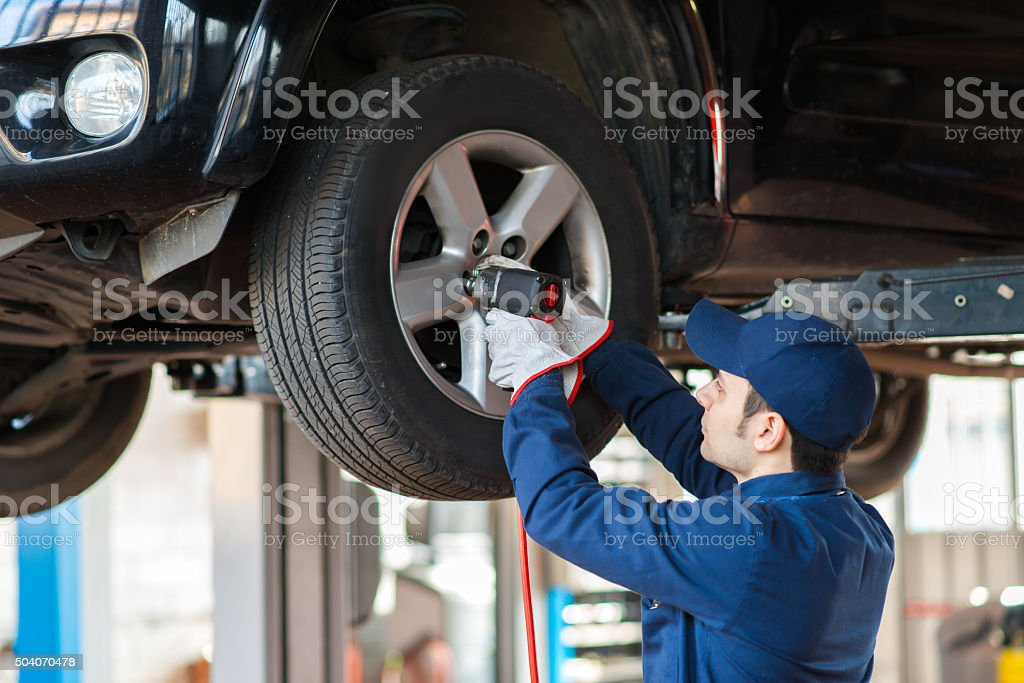 Portrait of a mechanic replacing wheel stock photo
