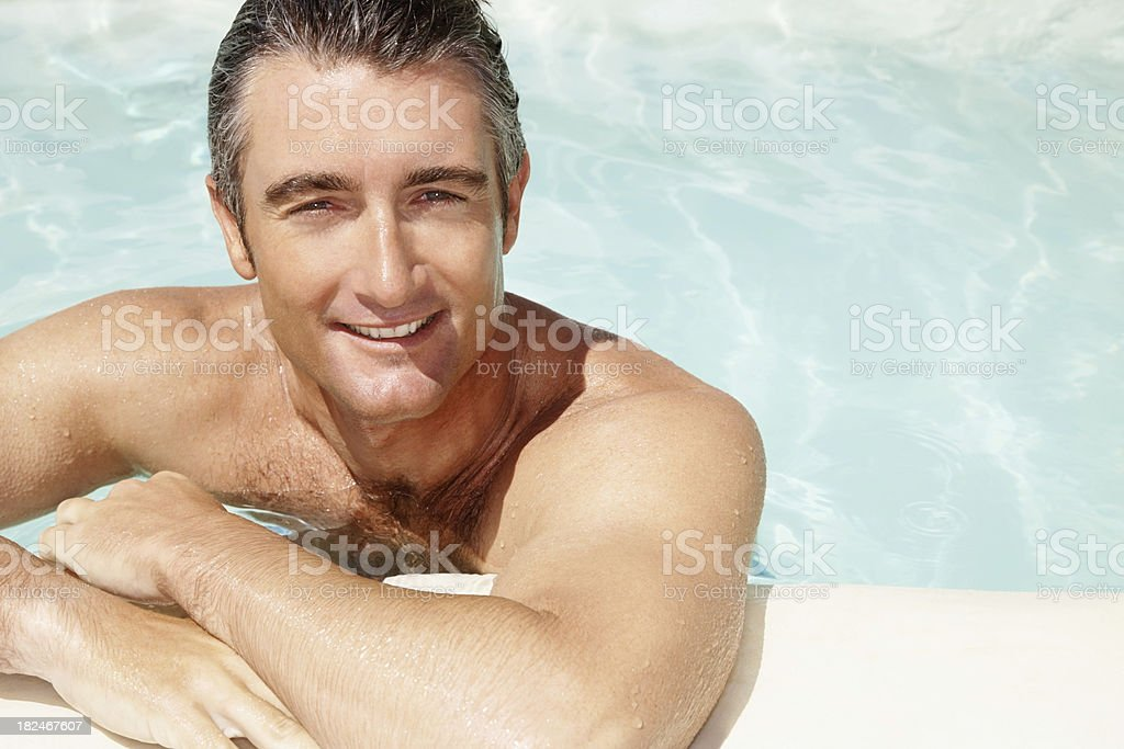 Portrait of a mid adult man smiling in swimming pool royalty-free stock photo