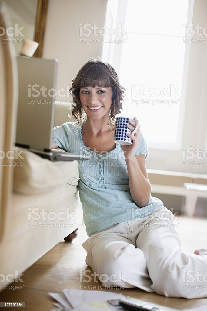 Portrait of a mid adult woman drinking coffee with laptop of sofa royalty-free stock photo