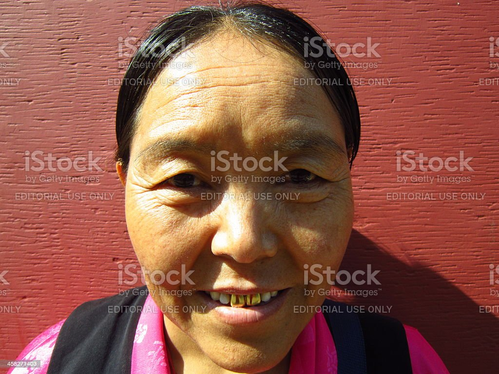 Portrait of a middle aged Tibetan woman with golden teeth. stock photo
