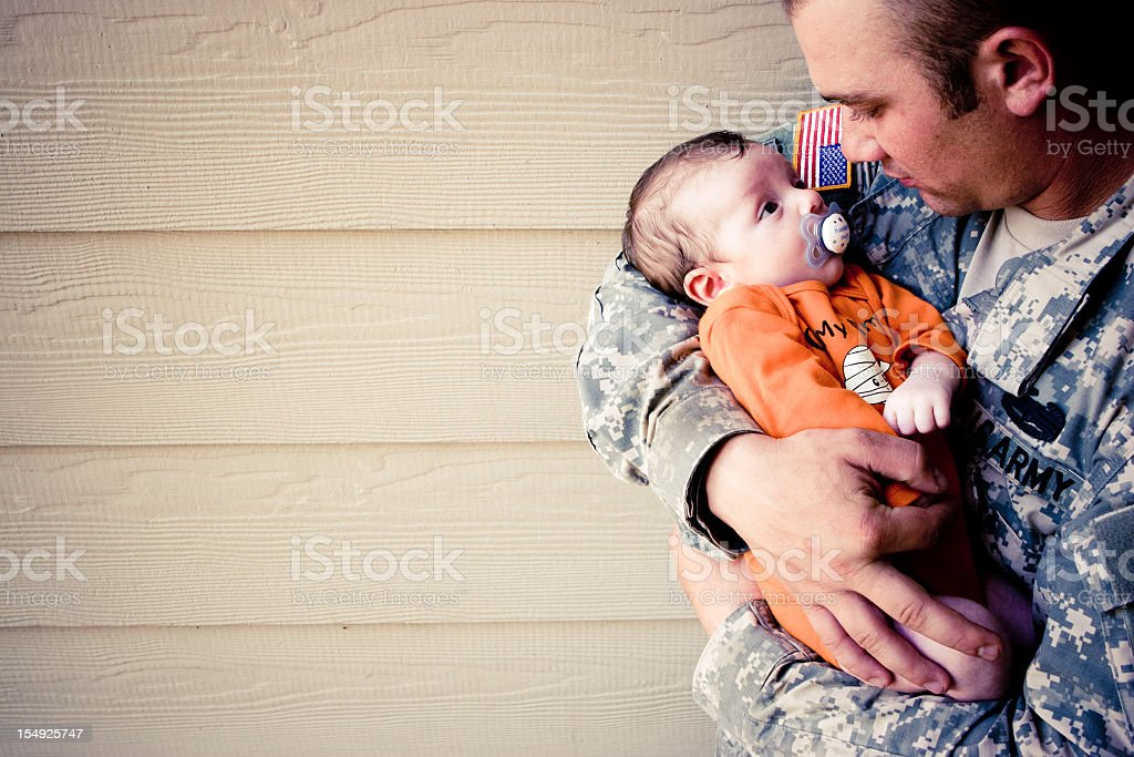 A portrait of a military man holding a young baby boy stock photo