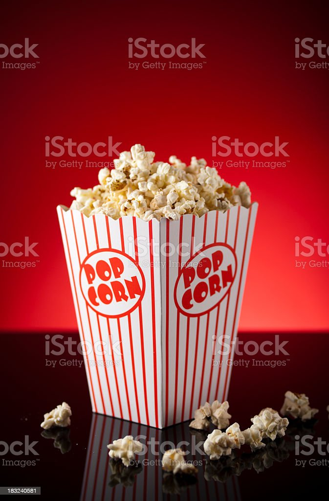 Portrait of a movie theater popcorn box overflowing royalty-free stock photo