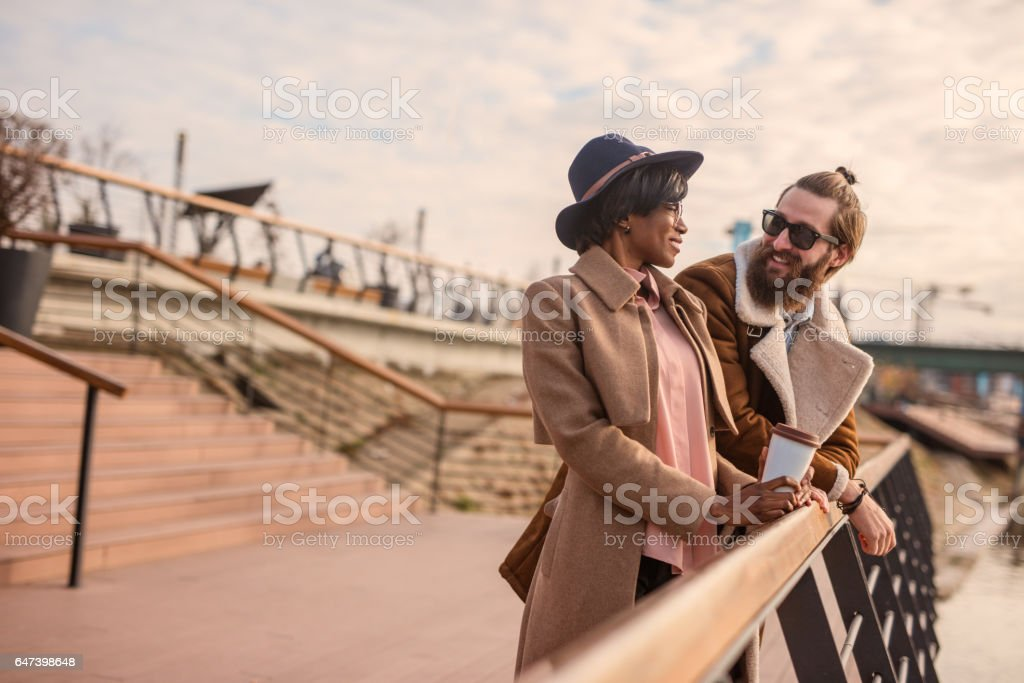 Portrait of a multi-ethnic couple leaned on a fence. Unshaven guy with his stylish female friend went out on a coffee outdoors stock photo