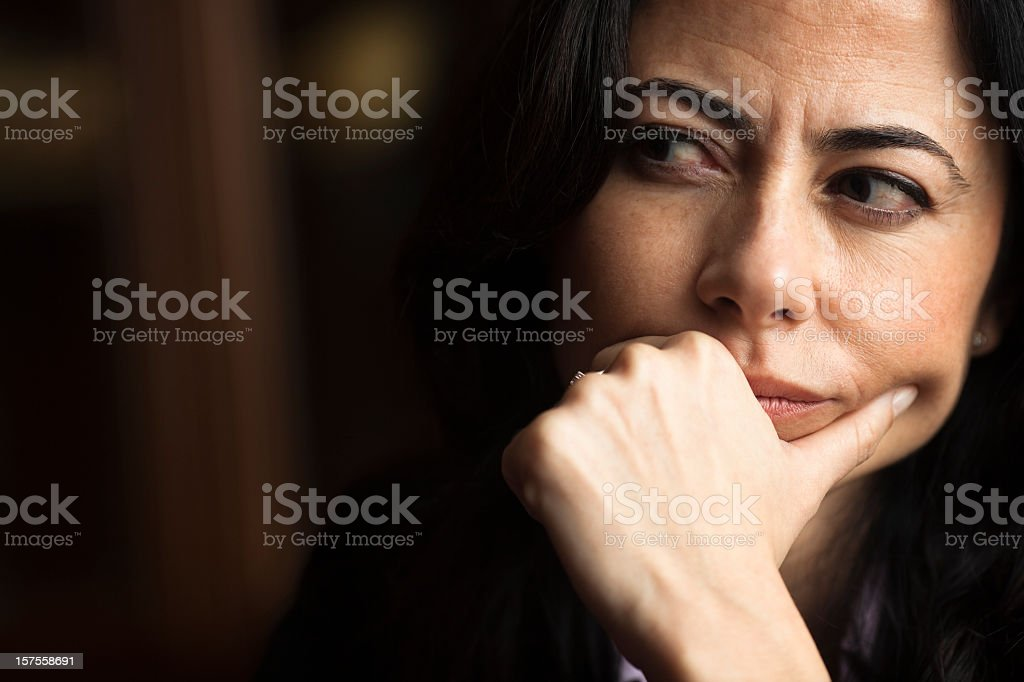 Portrait of a pensive woman with a furrowed brow stock photo