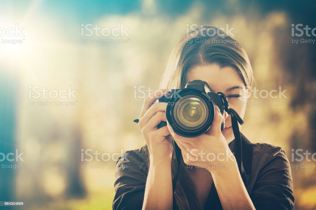 Portrait of a photographer covering her face with camera. stock photo