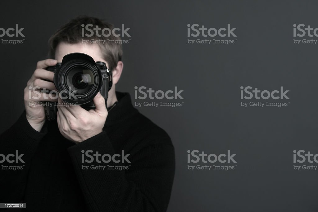 Portrait of a photographer with camera in front of his face stock photo