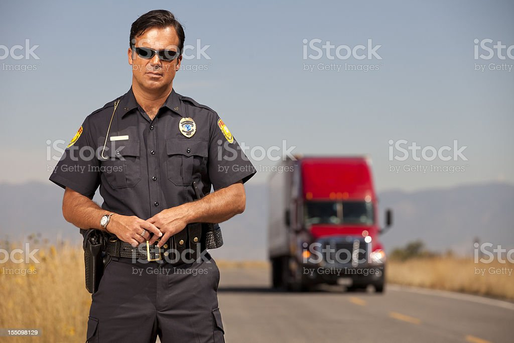 Portrait of a Police Officer and Cargo Truck stock photo