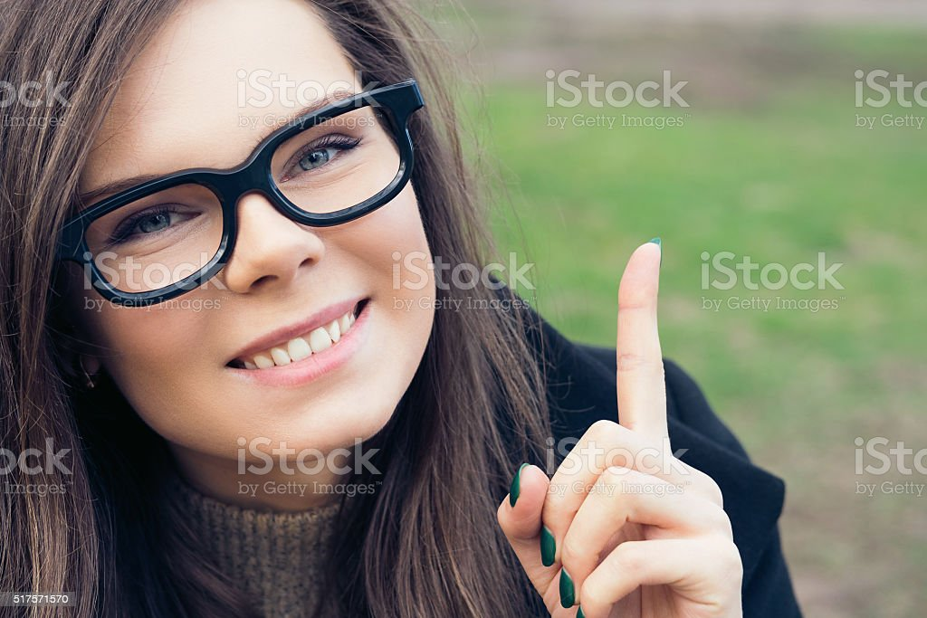 Portrait of a pretty girl raised an index finger upwards stock photo