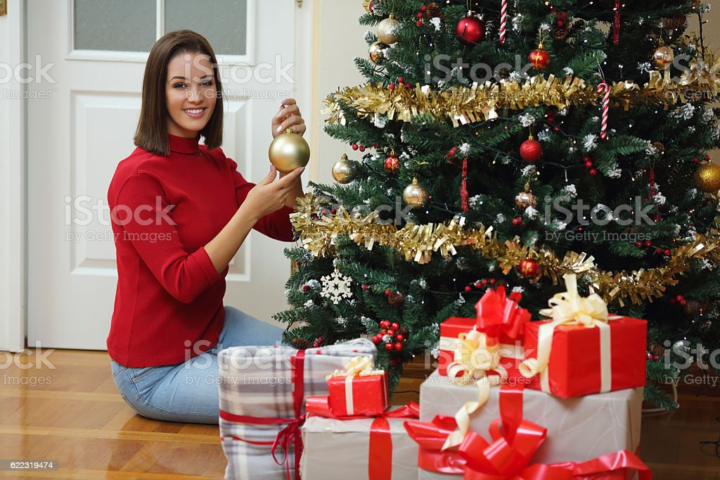 Portrait of a pretty young woman decorating the Christmas tree stock photo
