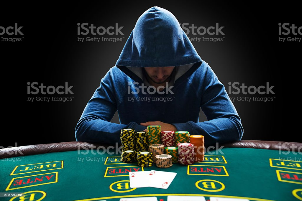 Portrait of a professional poker player sitting at pokers table stock photo