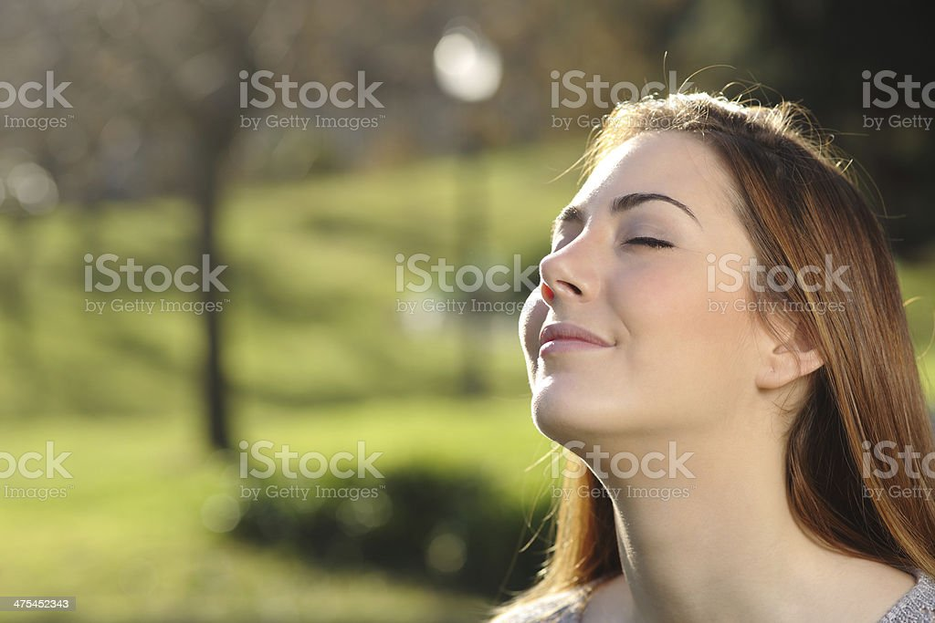 Portrait of a relaxed woman breathing deep in a park stock photo