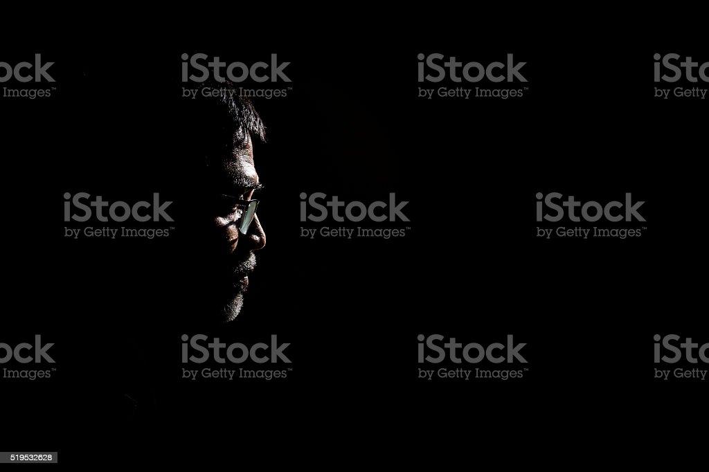 Portrait of a senior man in dark background. stock photo