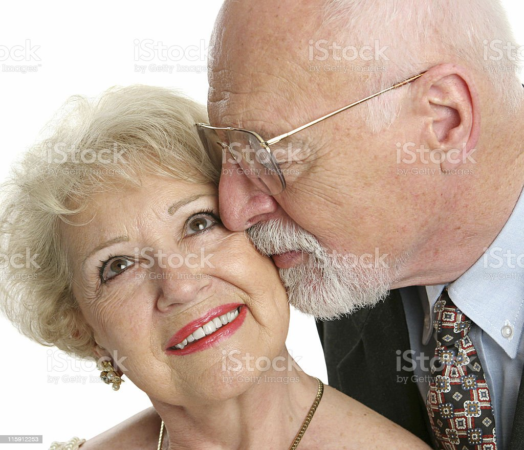Portrait of a senior man kissing his wife on the cheek stock photo