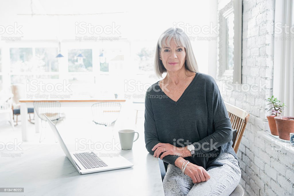Portrait of a senior woman at desk with laptop stock photo