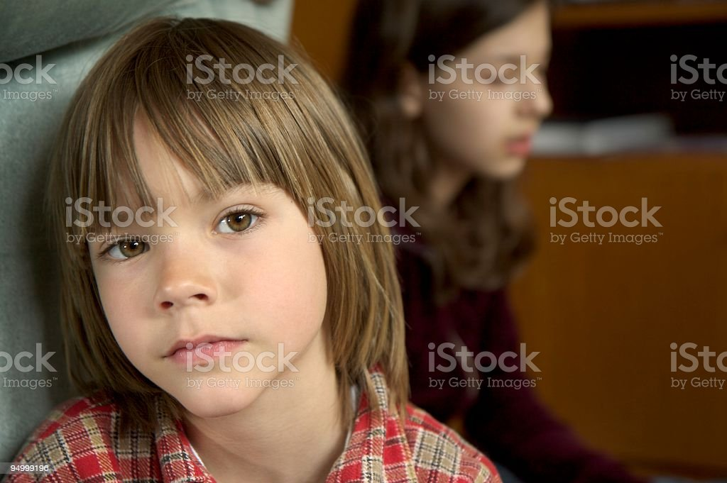 Portrait of a serious boy, looks sad, sister in background royalty-free stock photo