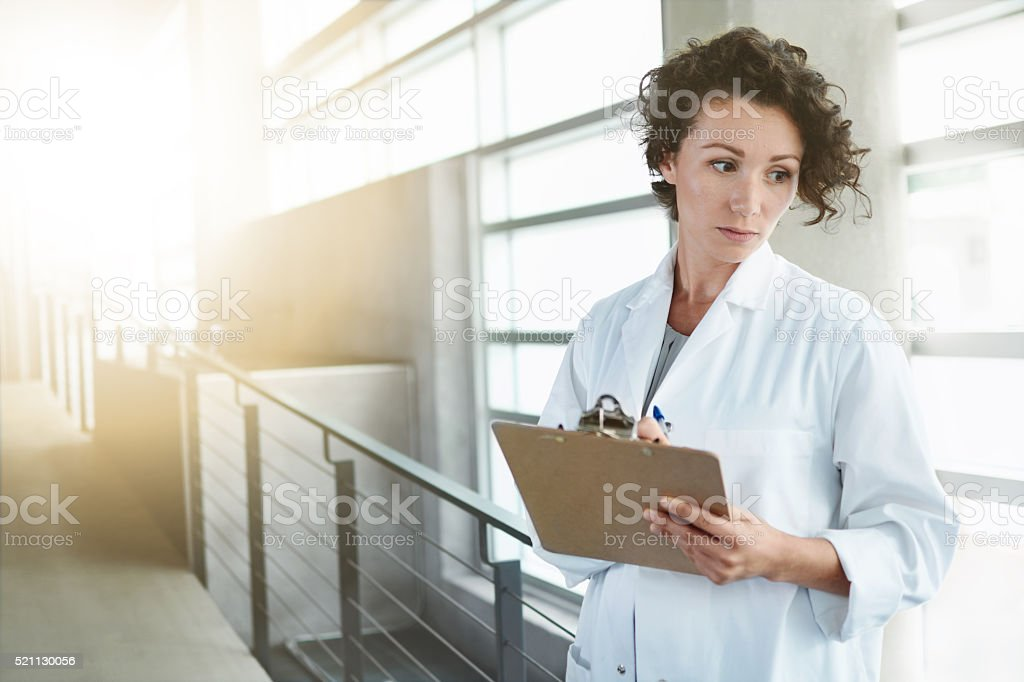 Portrait of a serious female doctor holding her patient chart stock photo