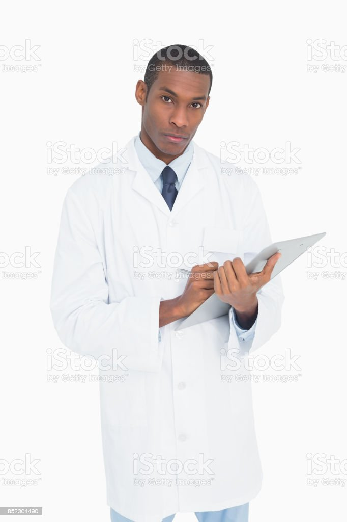 Portrait of a serious male doctor with clipboard stock photo
