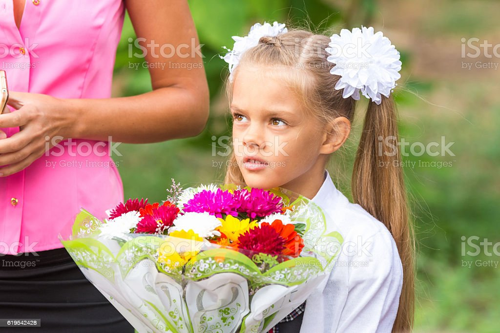 Portrait of a seven-year schoolgirl, standing next to my mother stock photo
