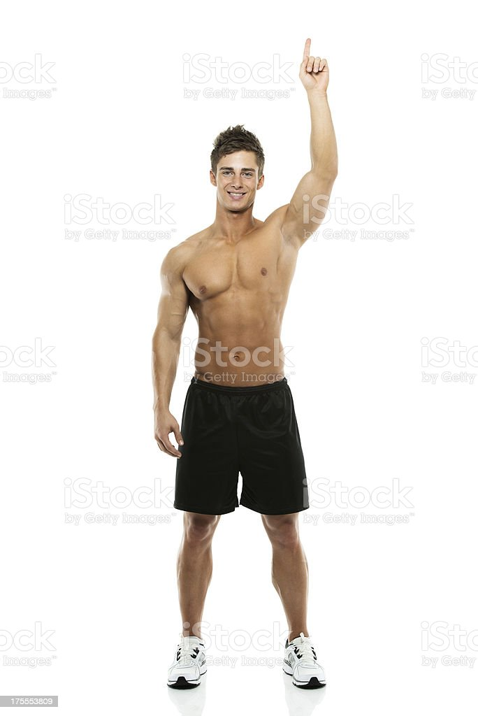 Portrait of a shirtless man pointing upwards royalty-free stock photo
