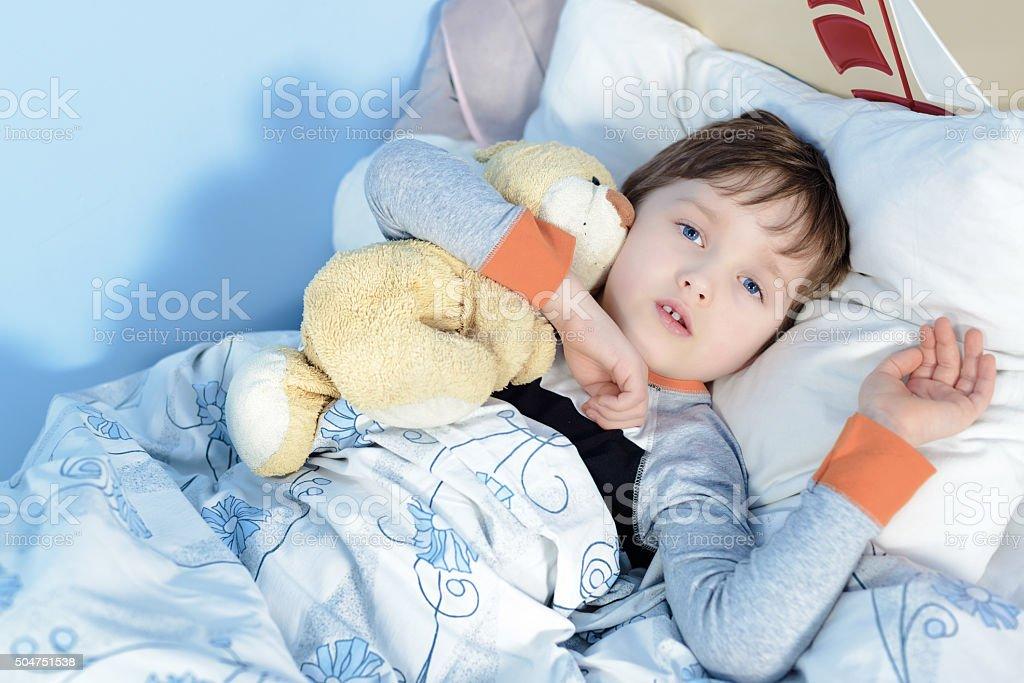 Portrait of a sick boy hugging a teddy bear stock photo