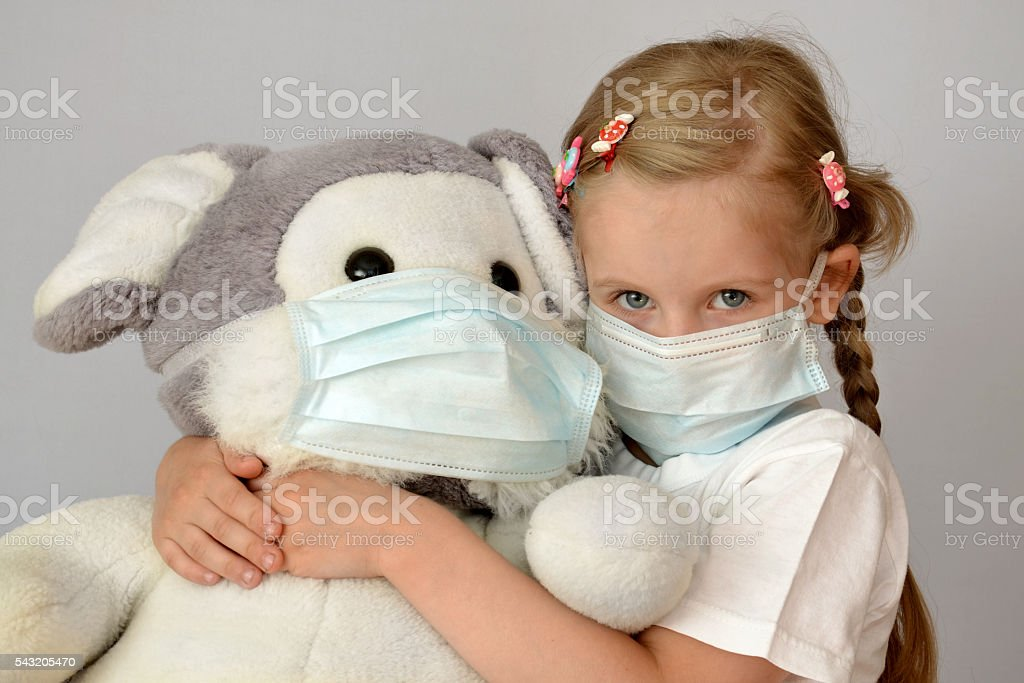 portrait of a sick child in a medical mask stock photo