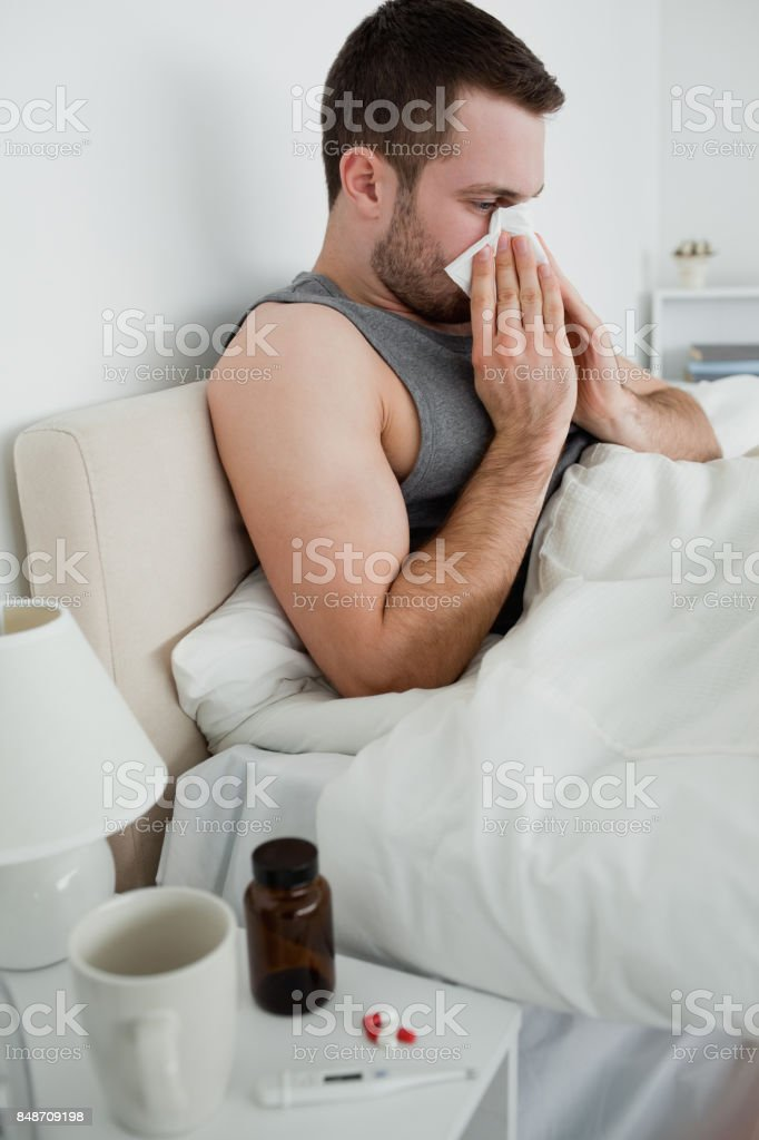 Portrait of a sick man blowing his nose stock photo