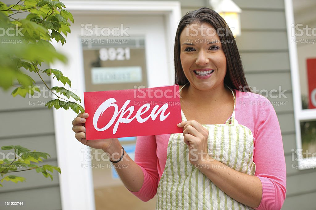 A portrait of a small business owner holding an open sign royalty-free stock photo