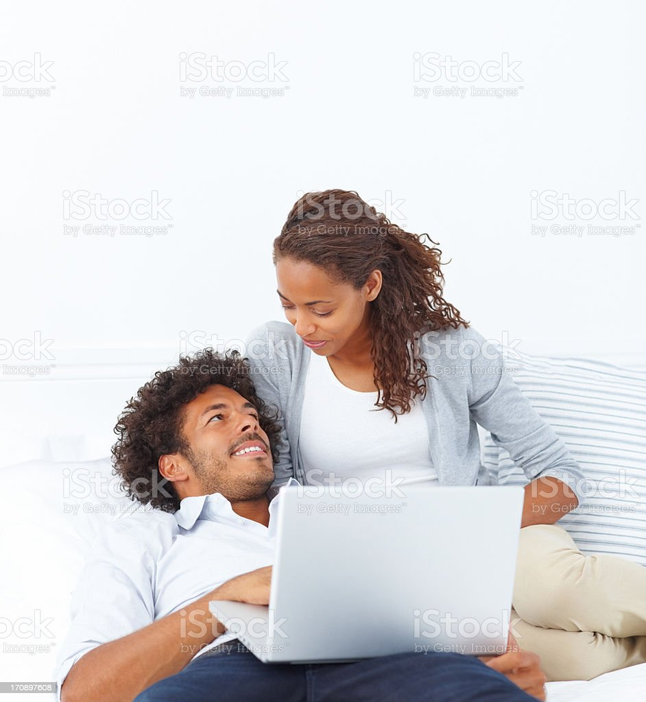 Portrait of a smart cheerful happy young couple lying on the bed with a laptop stock photo