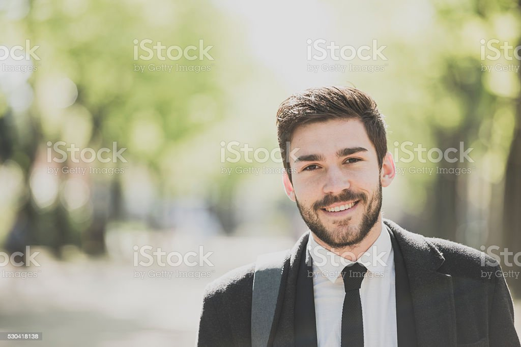 Portrait of a smart young man outdoors smiling stock photo