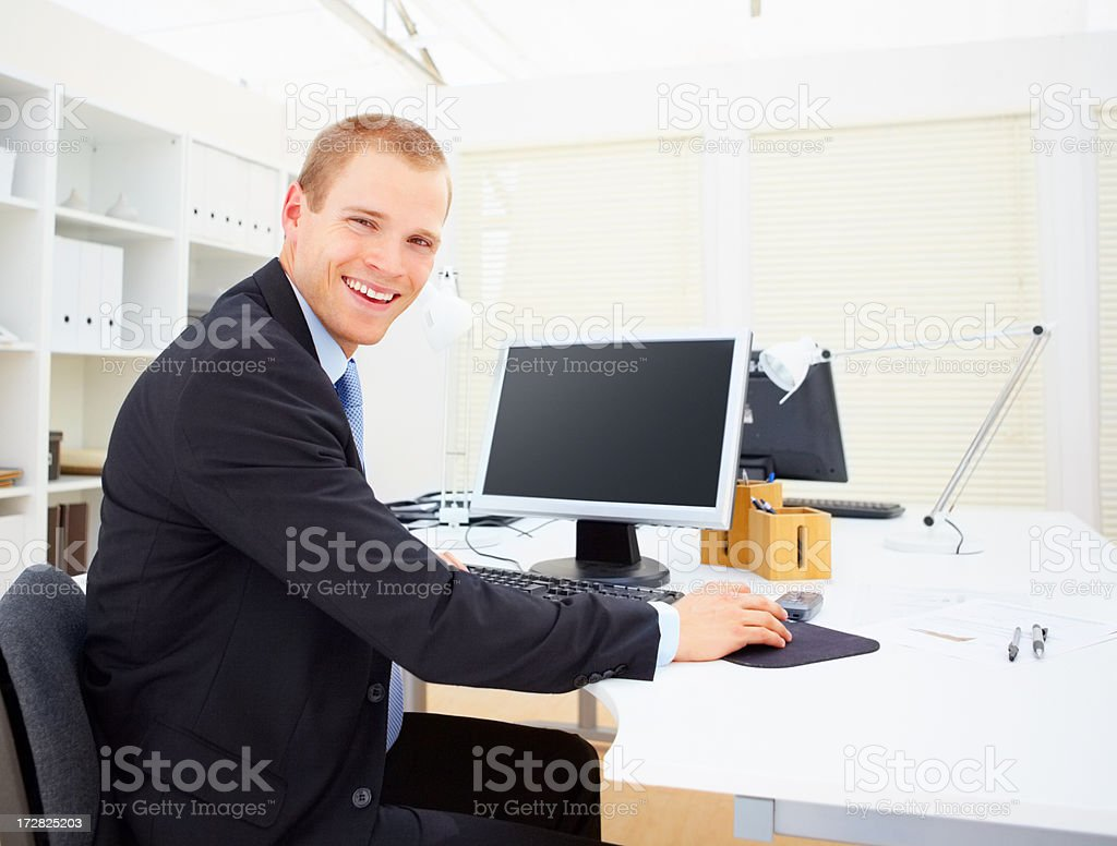 Portrait of a smiling business executive using a computer stock photo