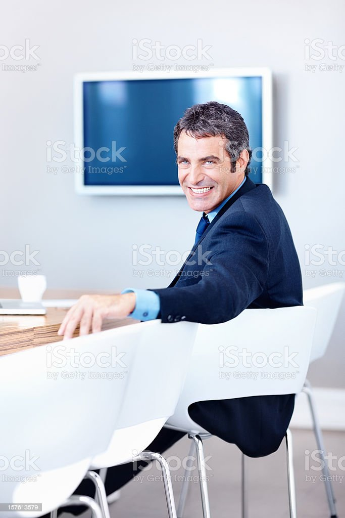 Portrait of a smiling business man sitting in boardroom royalty-free stock photo