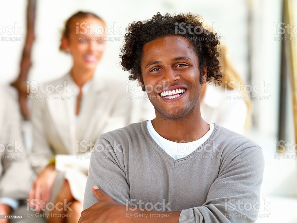 Portrait of a smiling business man with female executives against white background stock photo