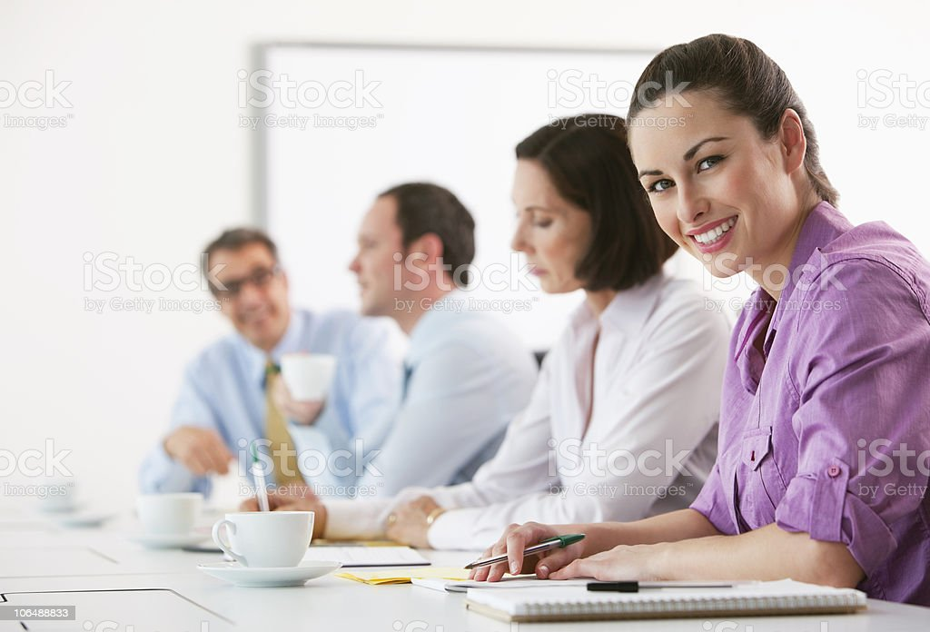Portrait of a smiling businesswoman with colleagues having coffee in board room royalty-free stock photo
