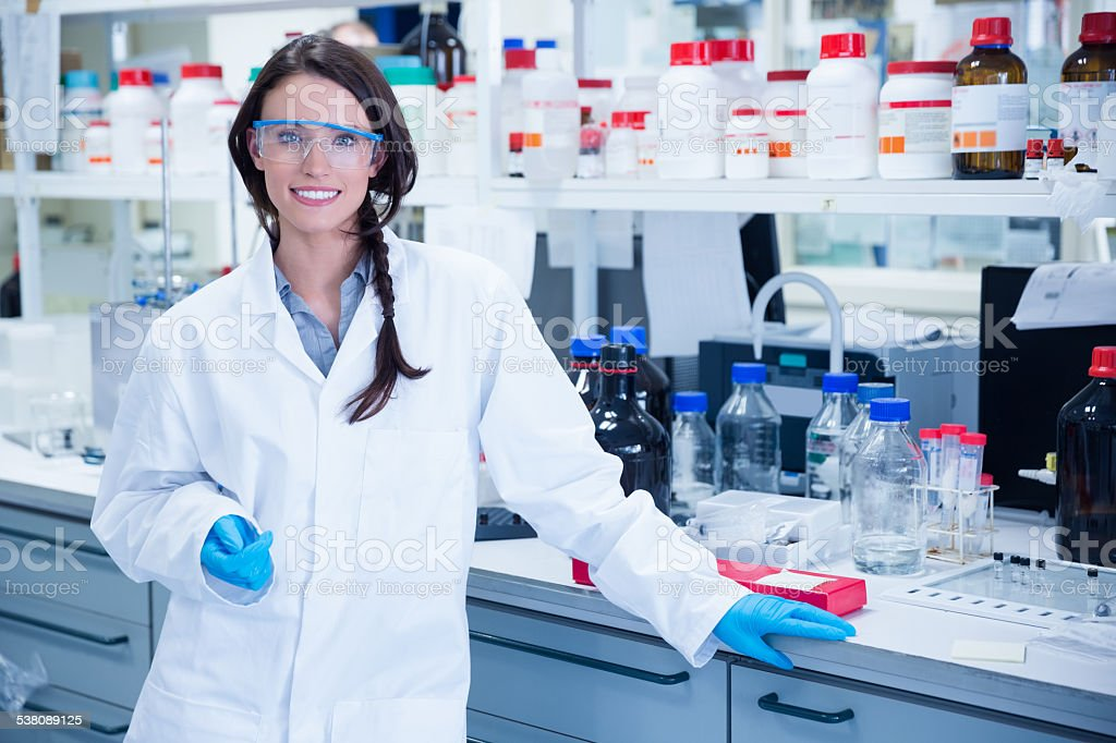 Portrait of a smiling chemist leaning against desk stock photo