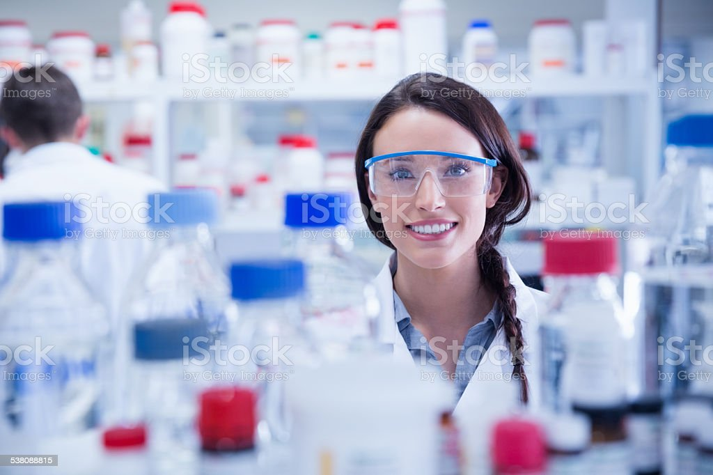 Portrait of a smiling chemist wearing safety glasses stock photo