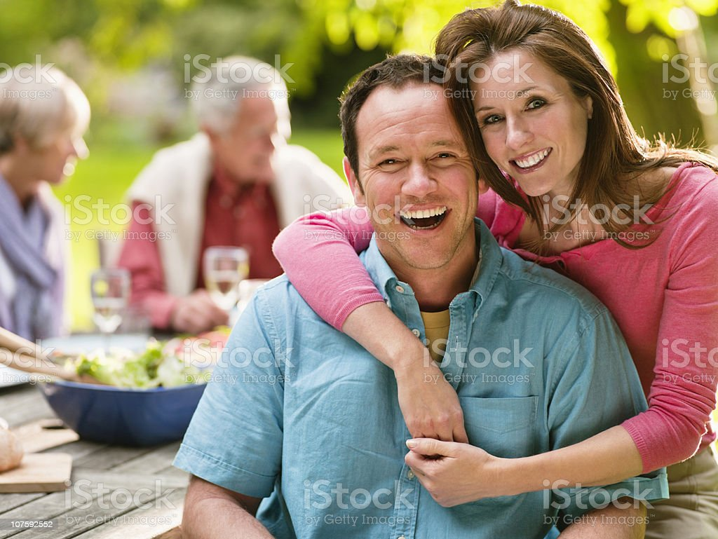 Portrait of a smiling couple on picnic with people in background royalty-free stock photo