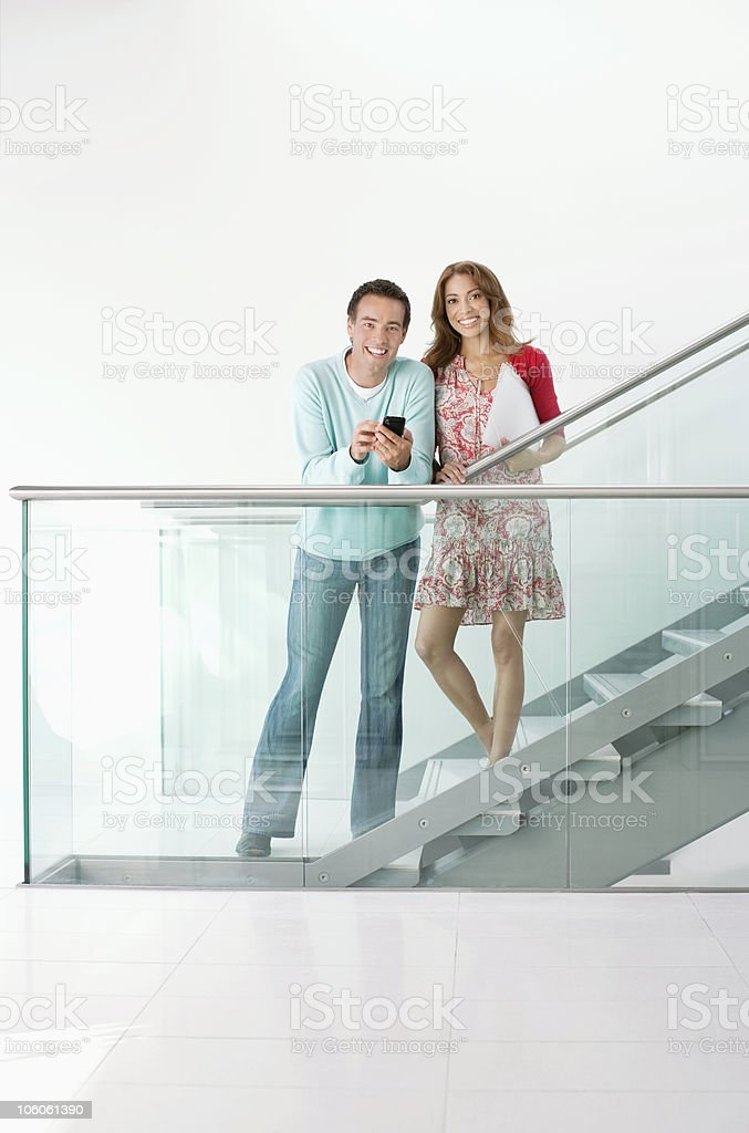 Portrait of a smiling couple with mobile phone standing on staircase royalty-free stock photo