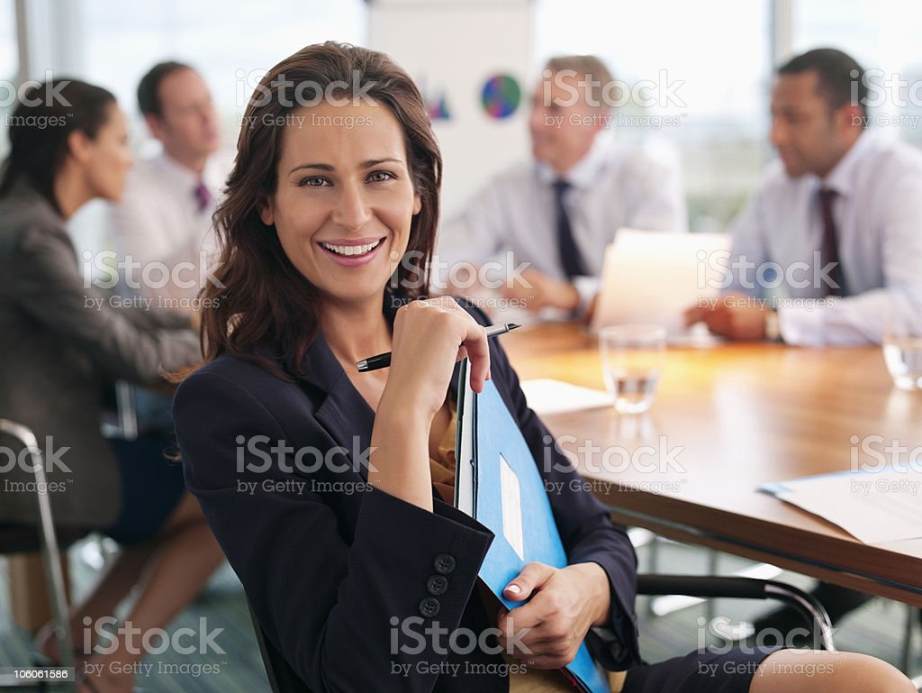 Portrait of a smiling executive holding files with colleagues discussing in background royalty-free stock photo
