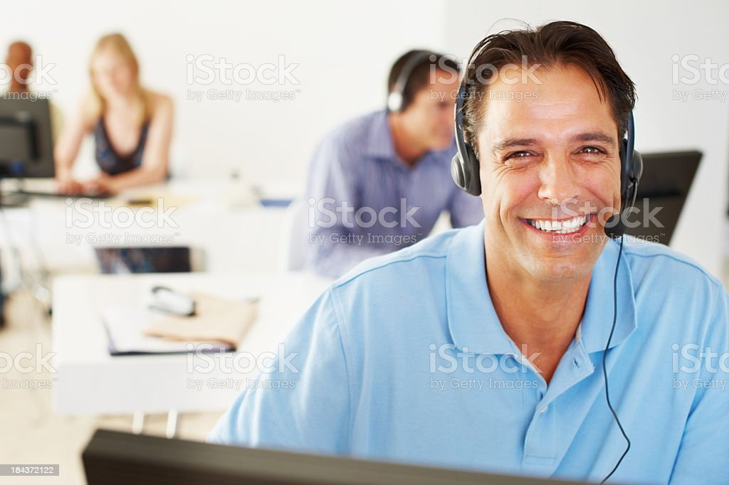 Portrait of a smiling man with a headset at a call service royalty-free stock photo