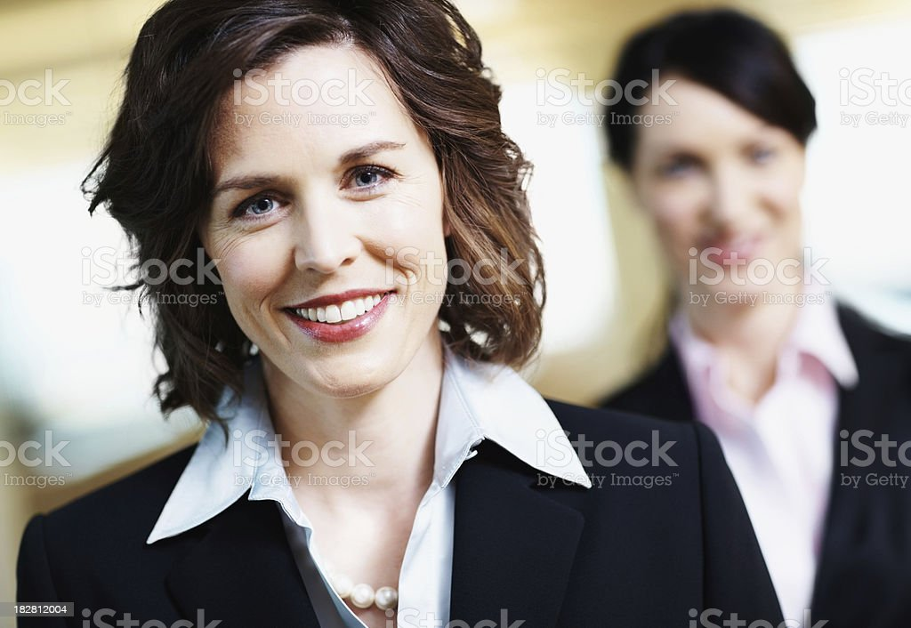Portrait of a smiling mature businesswoman with colleague at background royalty-free stock photo