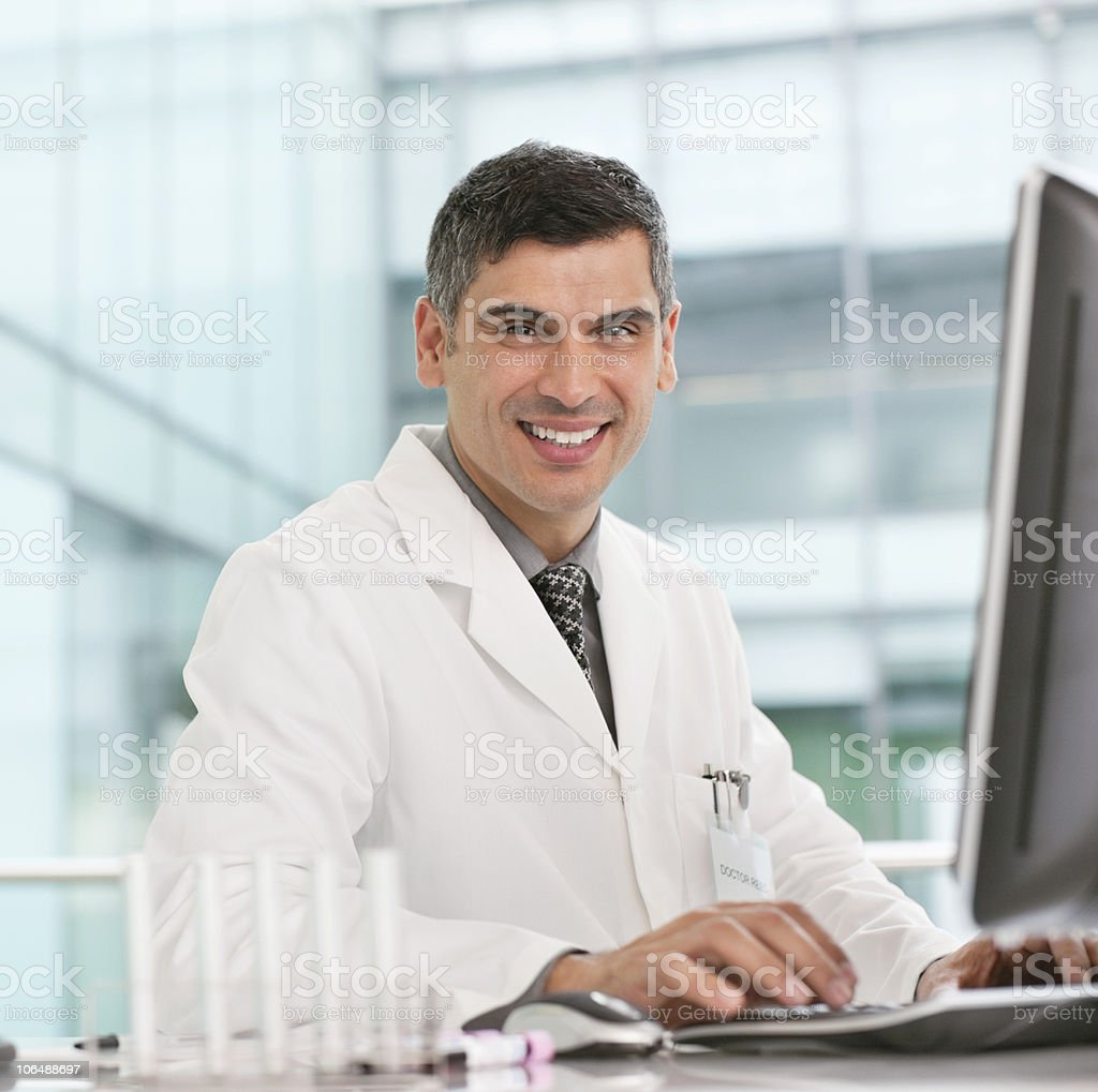 Portrait of a smiling mature man working on computer in laboratory stock photo