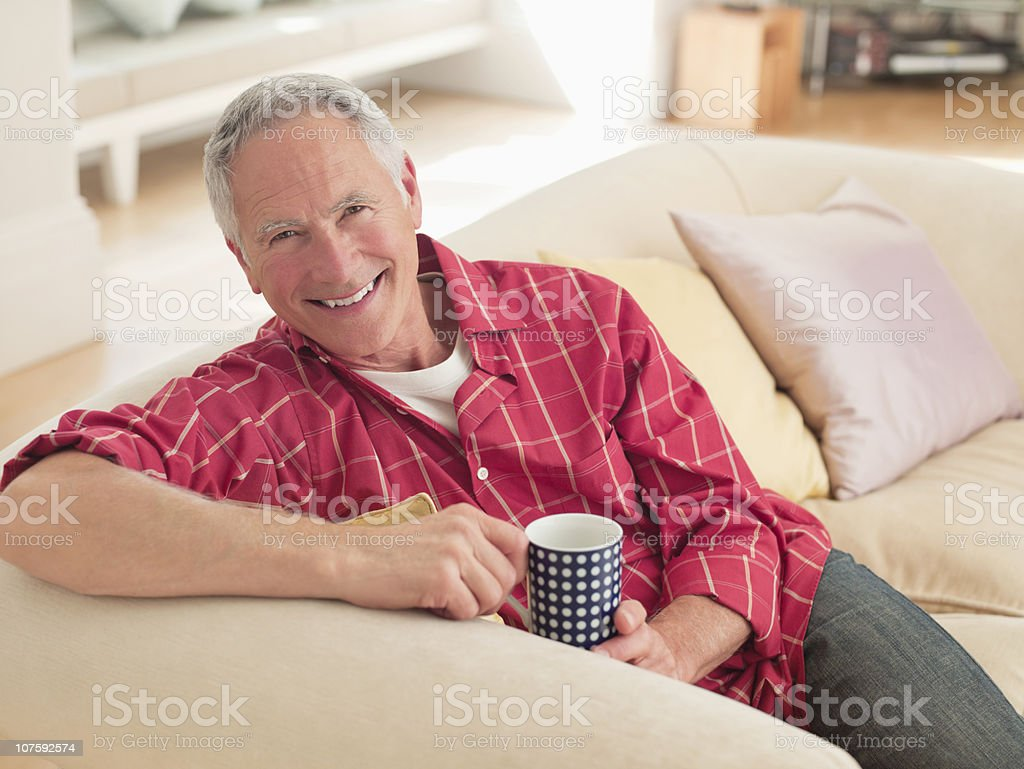 Portrait of a smiling senior man holding coffee cup sitting on couch royalty-free stock photo