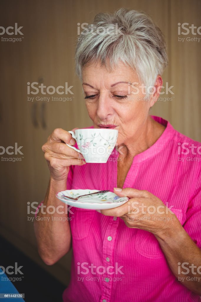 Portrait of a smiling woman drinking a tea stock photo