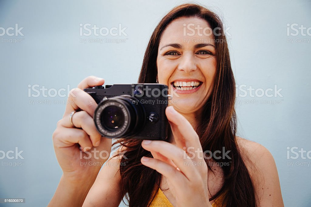 Portrait of a smiling woman taking a photo stock photo