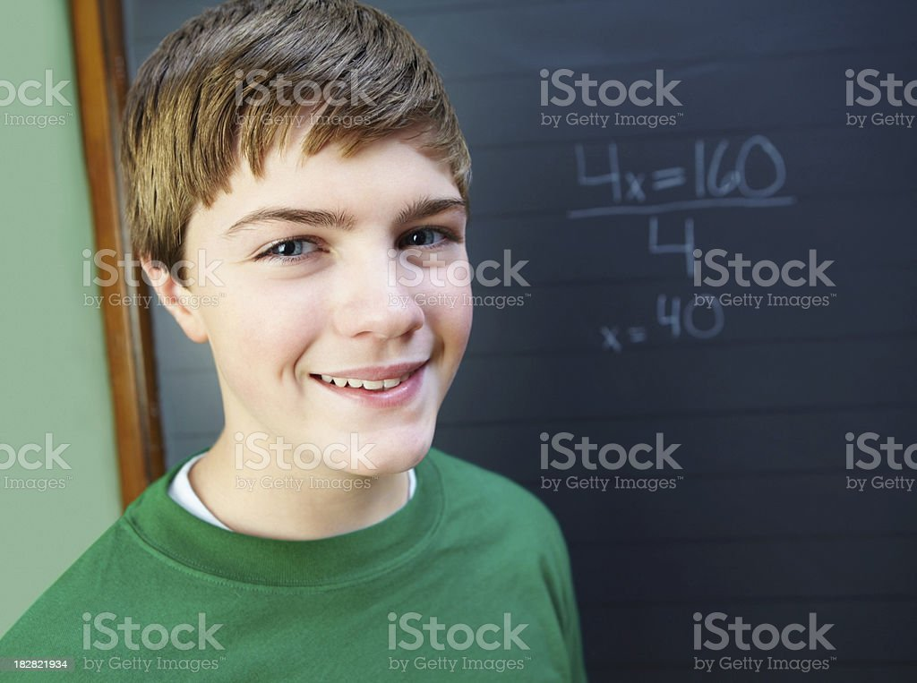 Portrait of a smiling young boy against black board royalty-free stock photo